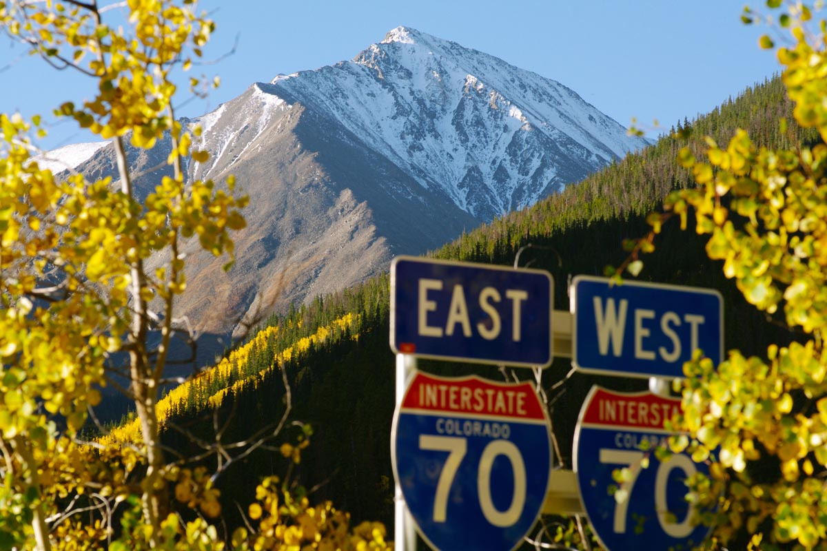 Interstate road signs foreground a high mountain peak.
