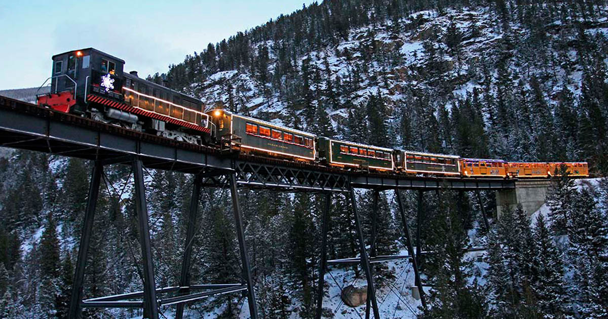 Historic holiday train travels a bridge far above the snowy ground below.